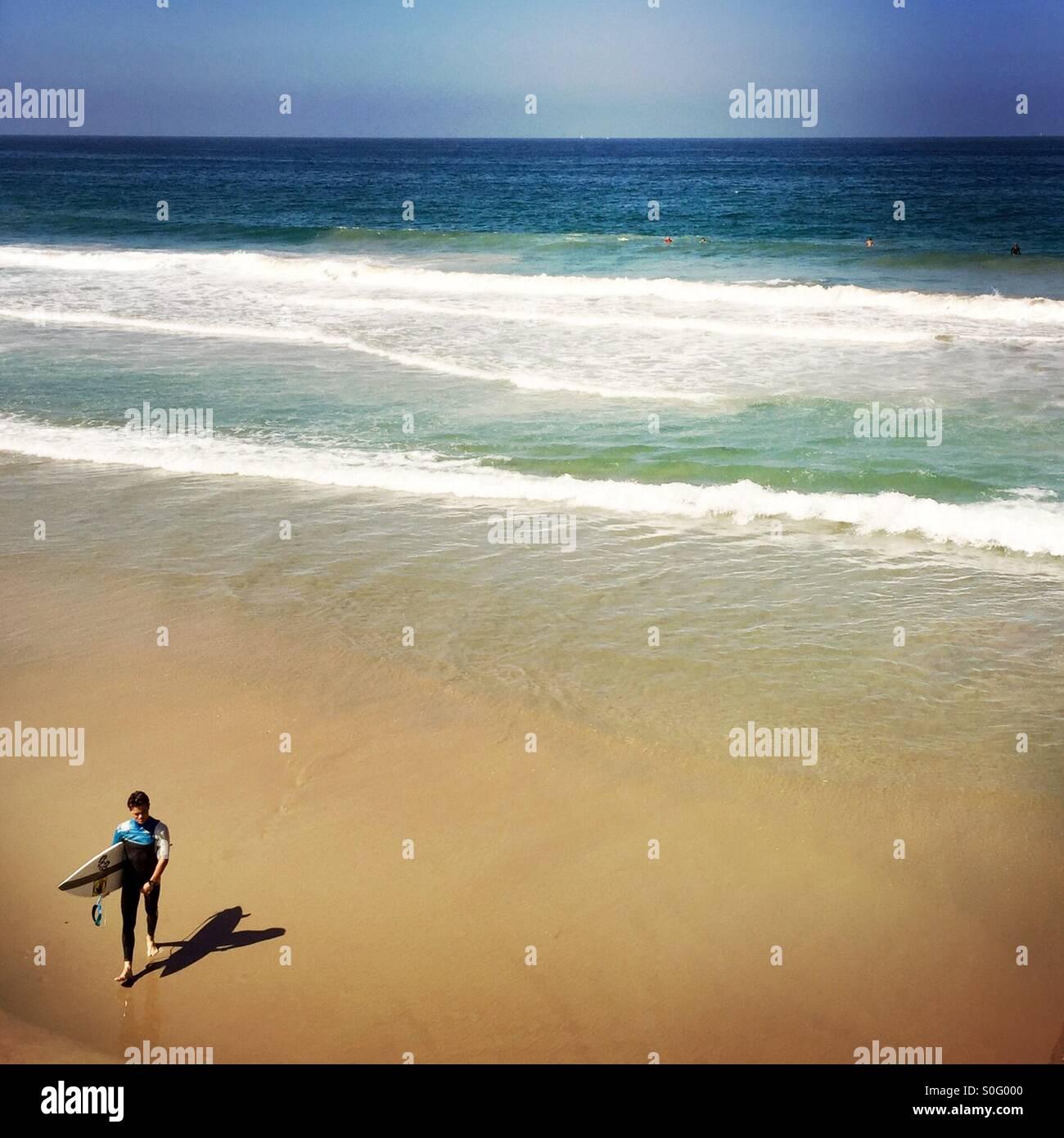 Un surfeur mâle s'approche de la plage. Manhattan Beach, en Californie. USA. Banque D'Images