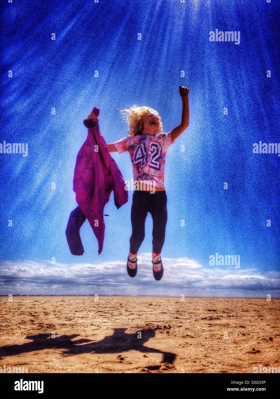 Jeune fille sautant de joie sur la plage à Lytham St Annes Photo Stock