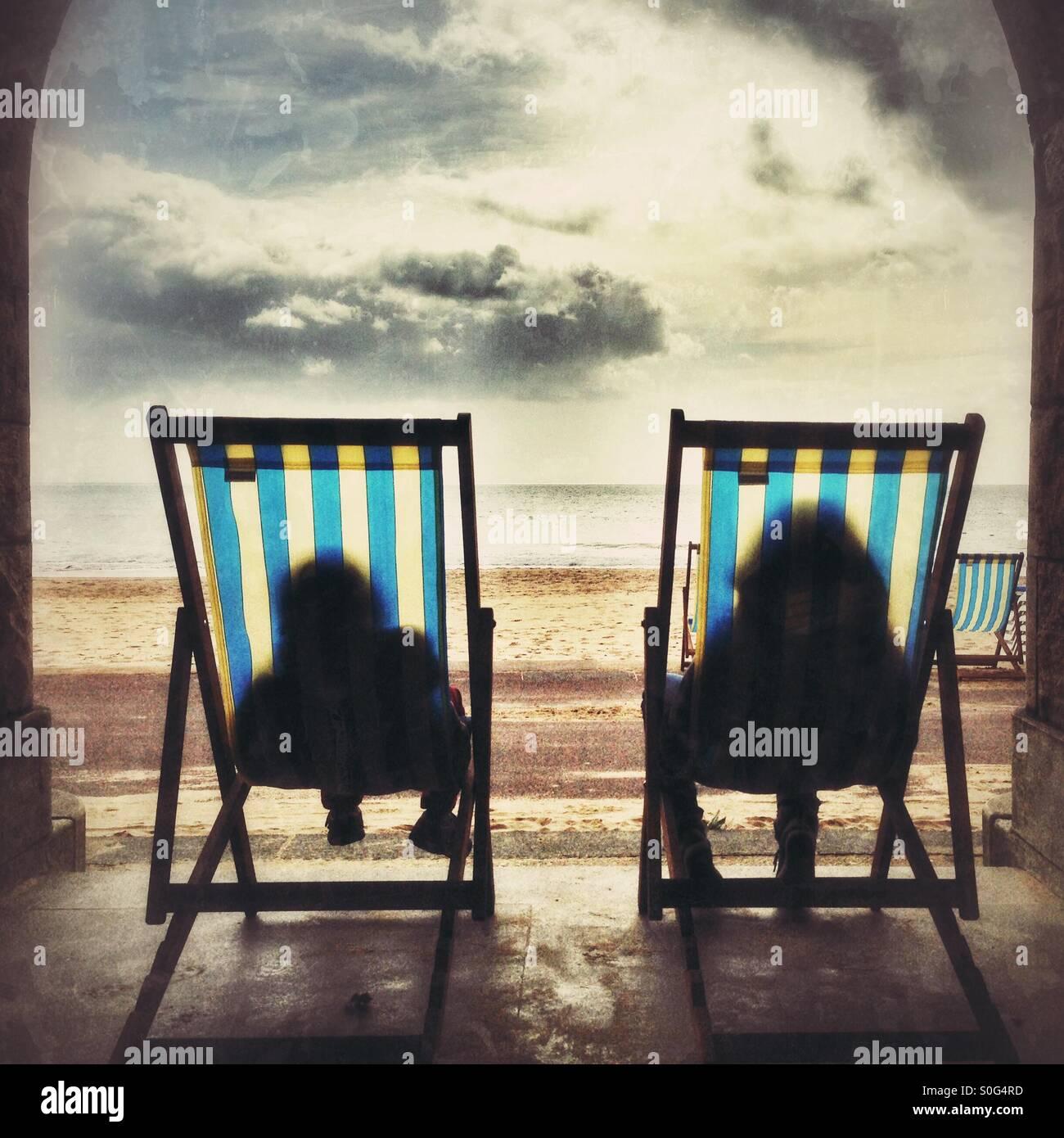 Vous relaxant dans des chaises longues à la plage de Bournemouth Photo Stock