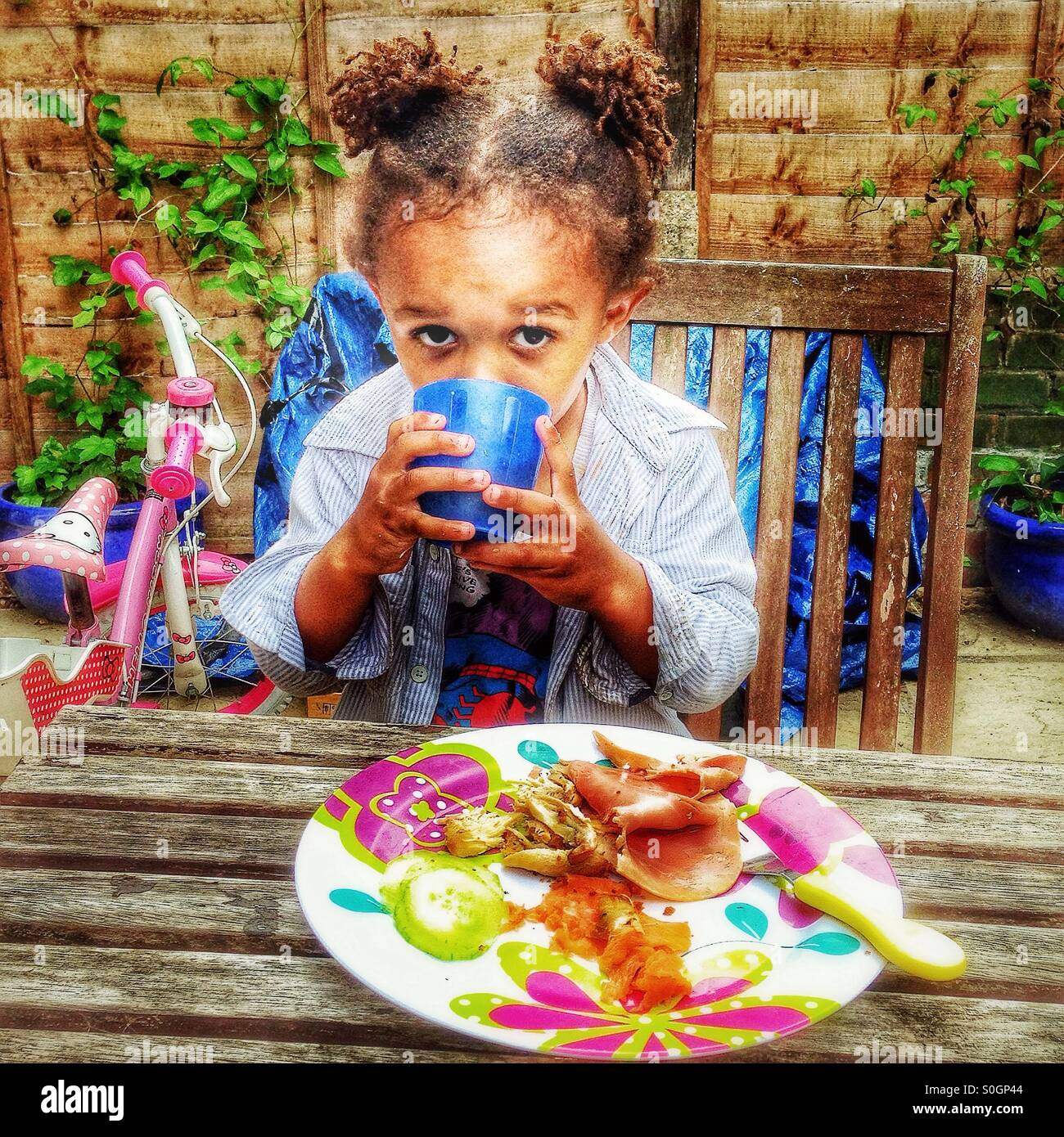 Un enfant a un repas dans le jardin. Photo Stock