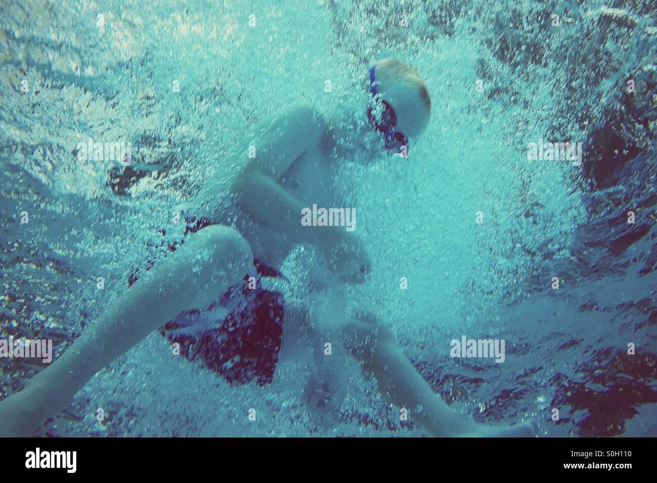 Underwater dynamique d'un jeune garçon de plonger dans l'eau, vue du dessous. Photo Stock