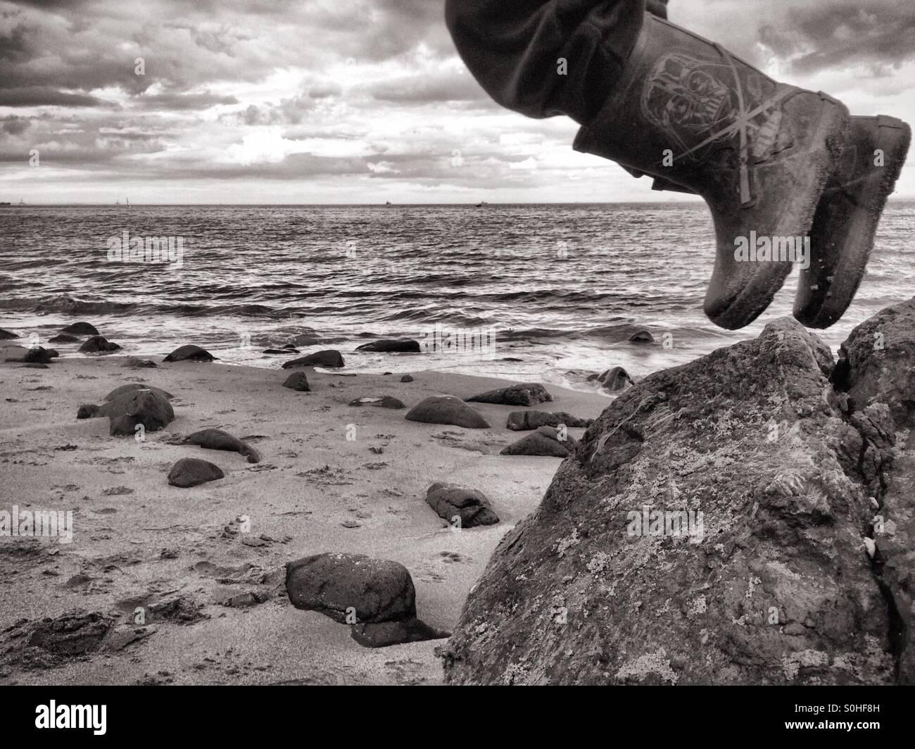 Sautant hors de l'enfant au rock beach Photo Stock