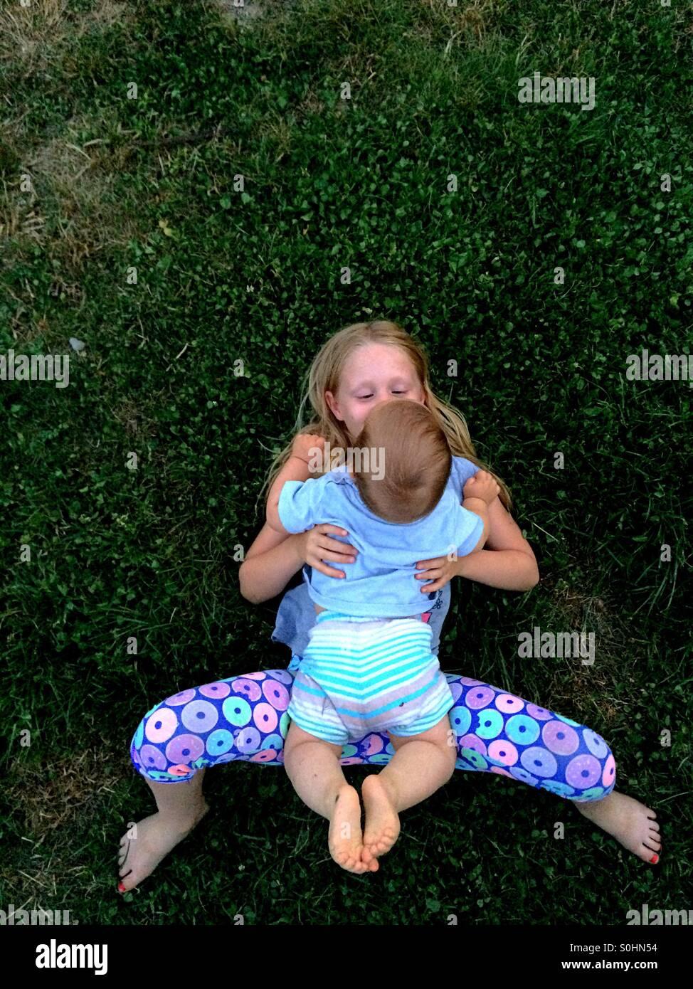Fille couchée sur l'herbe à l'extérieur avec son frère Photo Stock