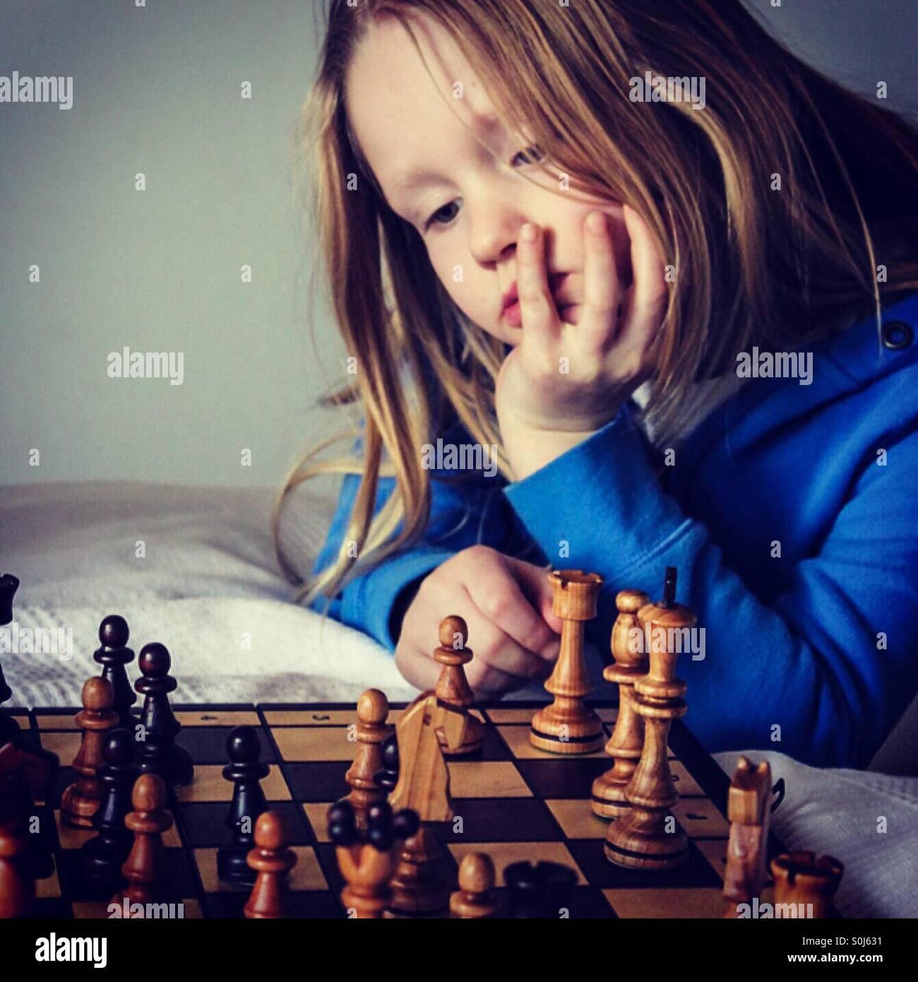Girl playing chess Photo Stock