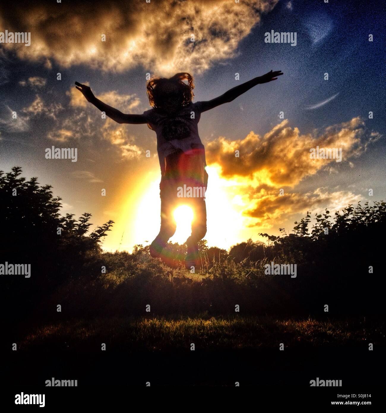 Jeune fille sautant de joie en silhouette contre le soleil couchant Photo Stock
