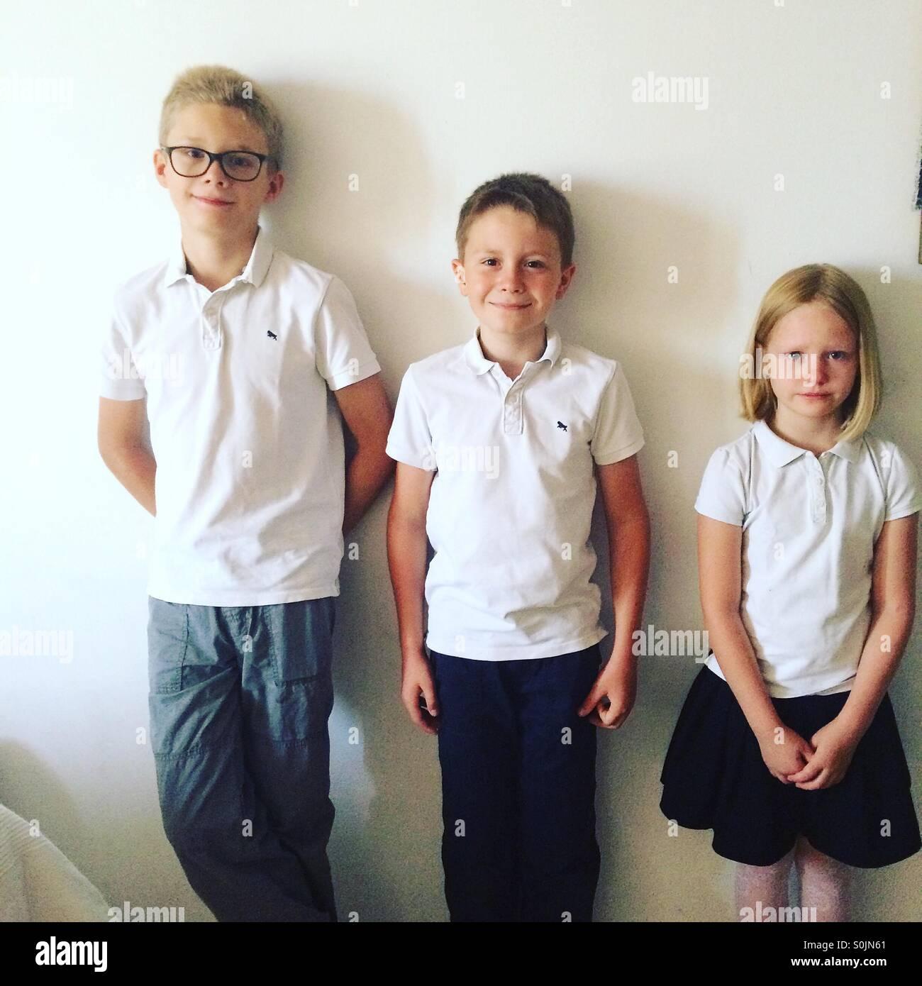 Trois enfants, frères et sœurs vêtus de tenues de nice , juste avant leur première journée d'école Photo Stock