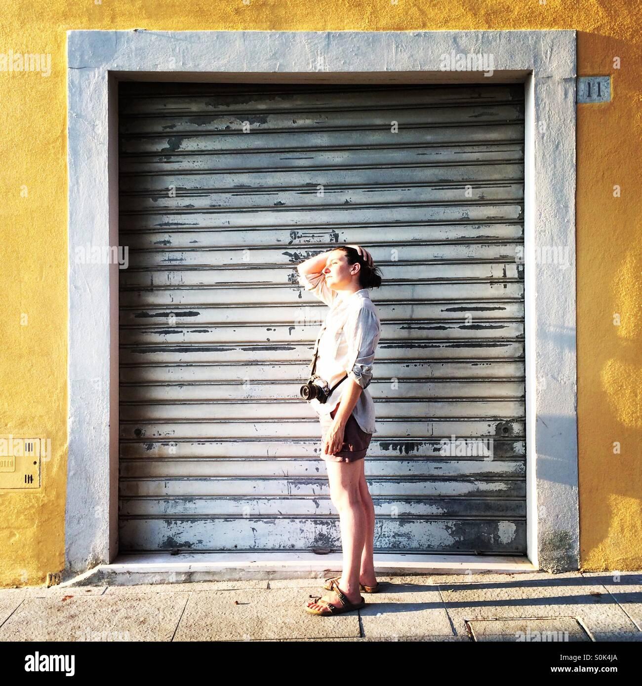 Une femme photographe avec son appareil photo à Arezzo, Toscane, encadré par une porte fermée. Photo Stock