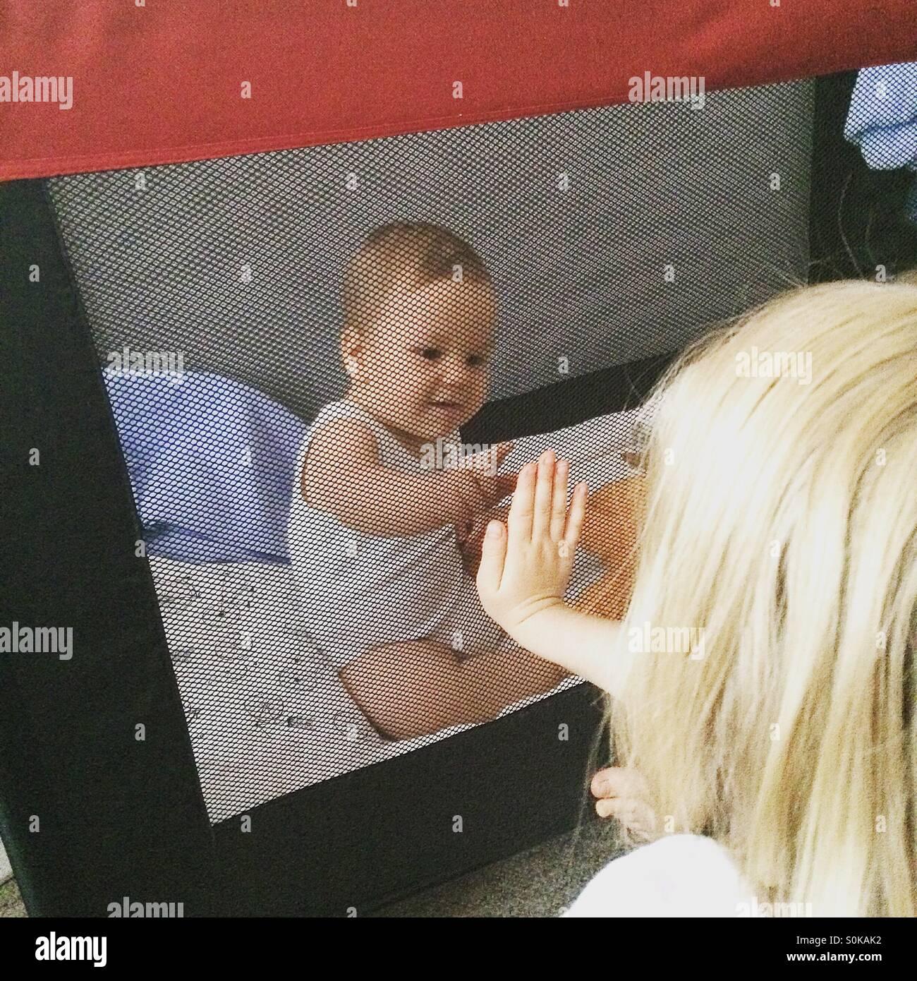 Deux frères jouent ensemble et se touchant les mains à travers le filet de la huche de portable Photo Stock