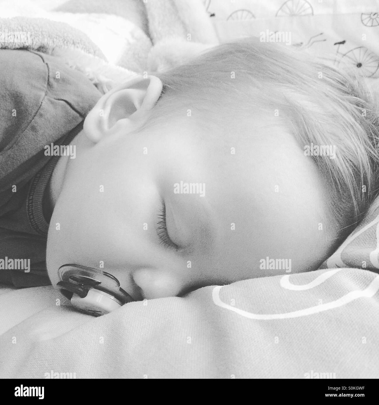 Un bébé de 9 mois garçon , ses dents, fiévreux est prendre une sieste avec sa sucette sur son Photo Stock