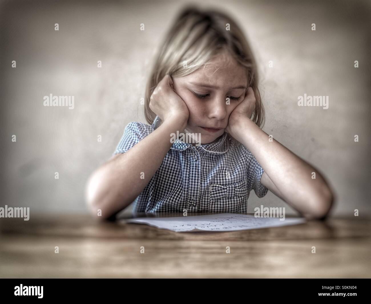 Fille de l'École de la difficulté à faire leurs devoirs Photo Stock