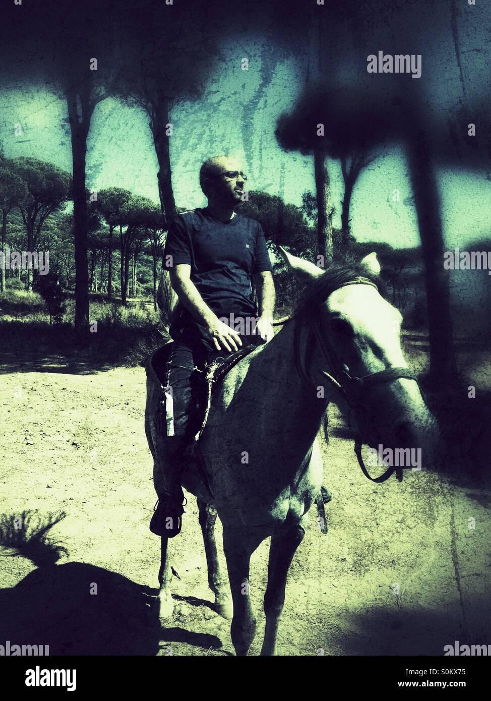 Middle aged man riding a horse avec fierté dans la forêt Photo Stock