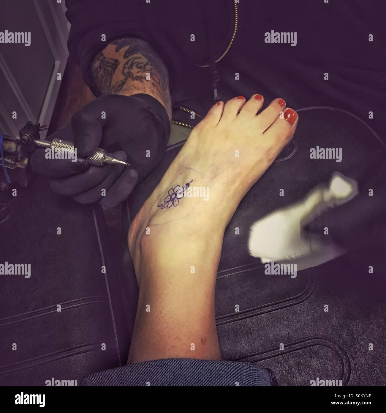 Artiste De Tatouage Tatouage Fleurs Expose Sur Pied De Femme D Age Moyen Premier Tattoo Photo Stock Alamy