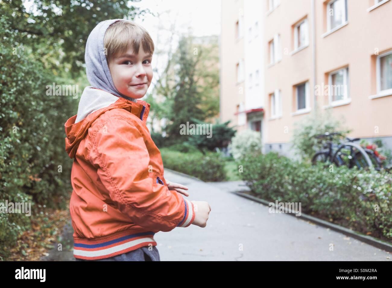 Portrait de jeune garçon d'âge préscolaire en milieu urbain, l'appareil photo en souriant Photo Stock