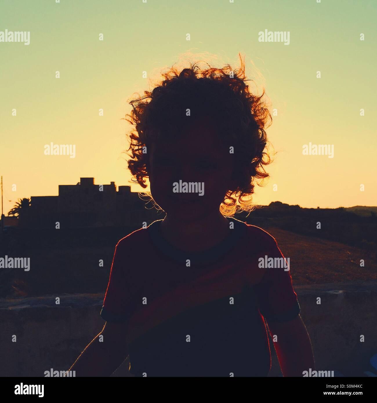 Silhouette rougeoyante du garçon avec coucher du soleil en arrière-plan Photo Stock