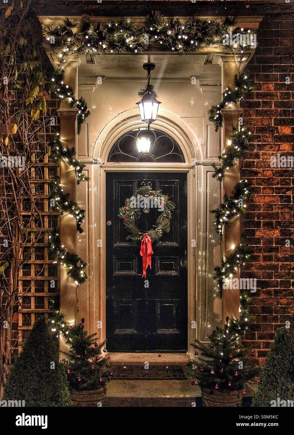 Une porte traditionnelle décorée pour Noël avec une couronne et des lumières. Photo Stock