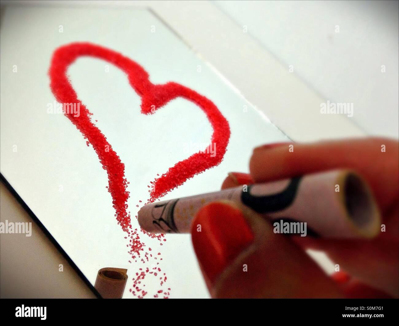 Quelqu'un à propos de snort en forme de coeur une substance en poudre. Banque D'Images