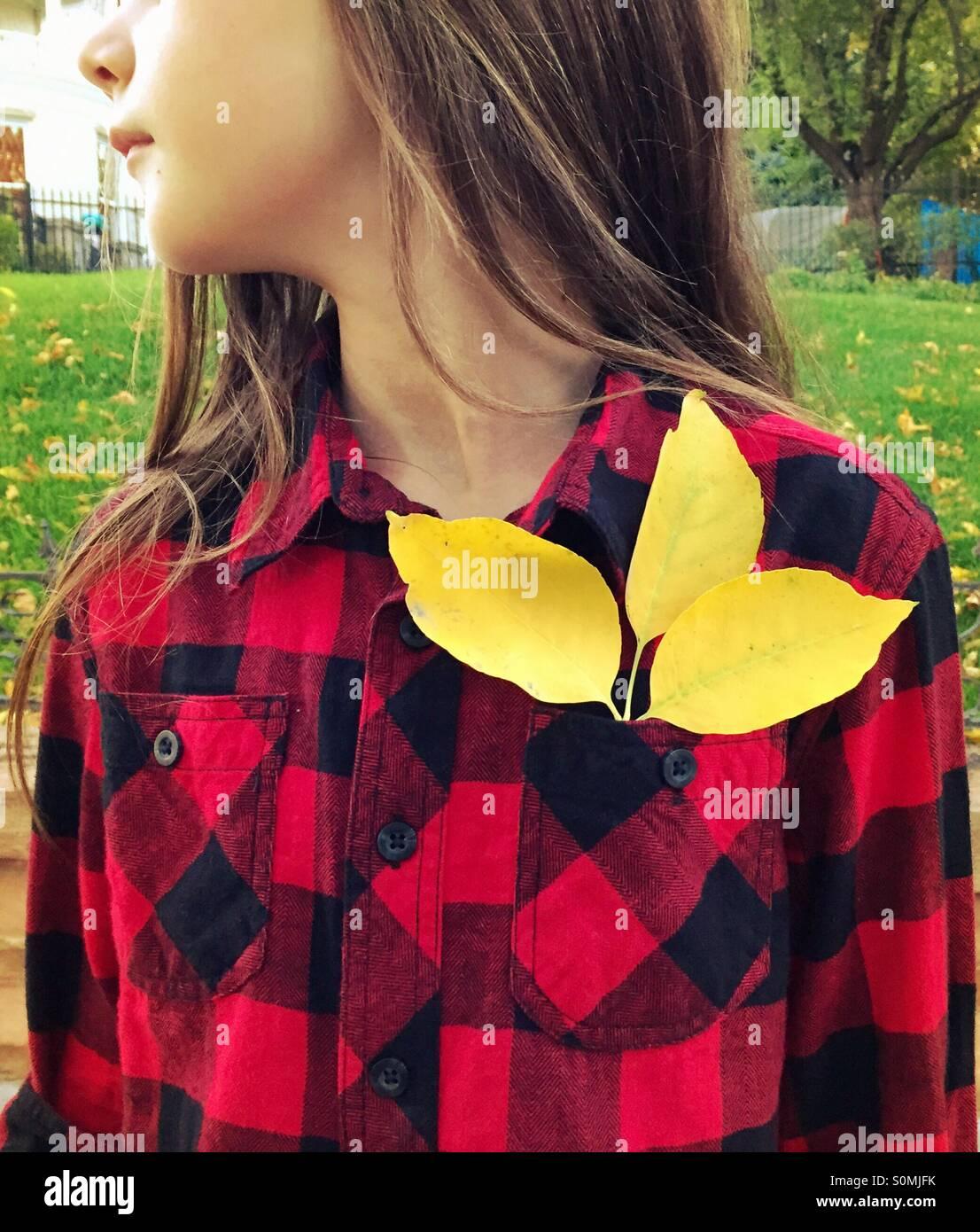 Une jeune fille porter du rouge et noir à carreaux chemise à carreaux buffalo a 3 feuilles jaunes dans Photo Stock