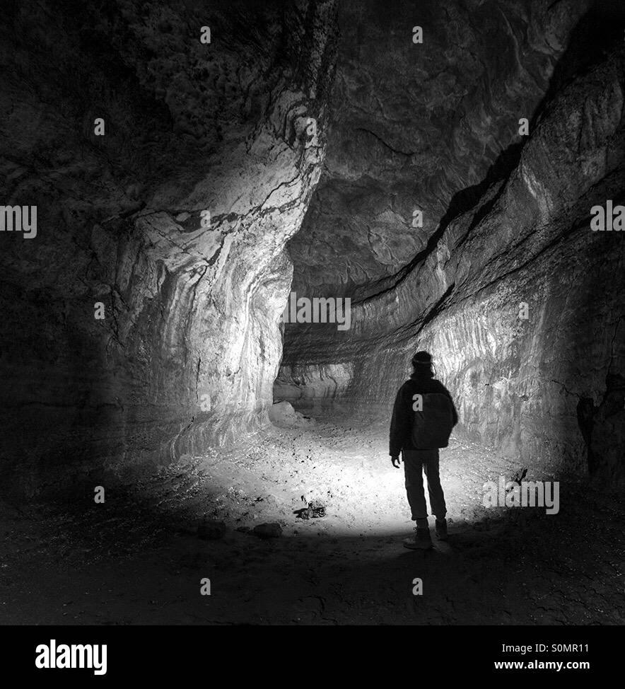 Silhouette d'un homme debout dans le tube de lave Photo Stock