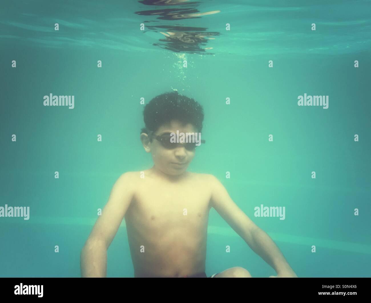 10 ans garçon nager sous l'eau dans la piscine Photo Stock
