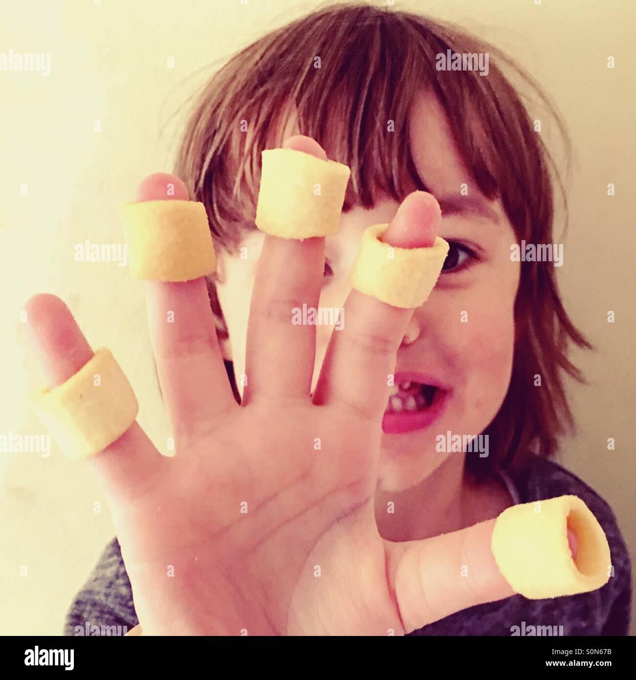 Petit garçon de 4 ans avec chips de pommes de terre sur ses doigts. Photo Stock
