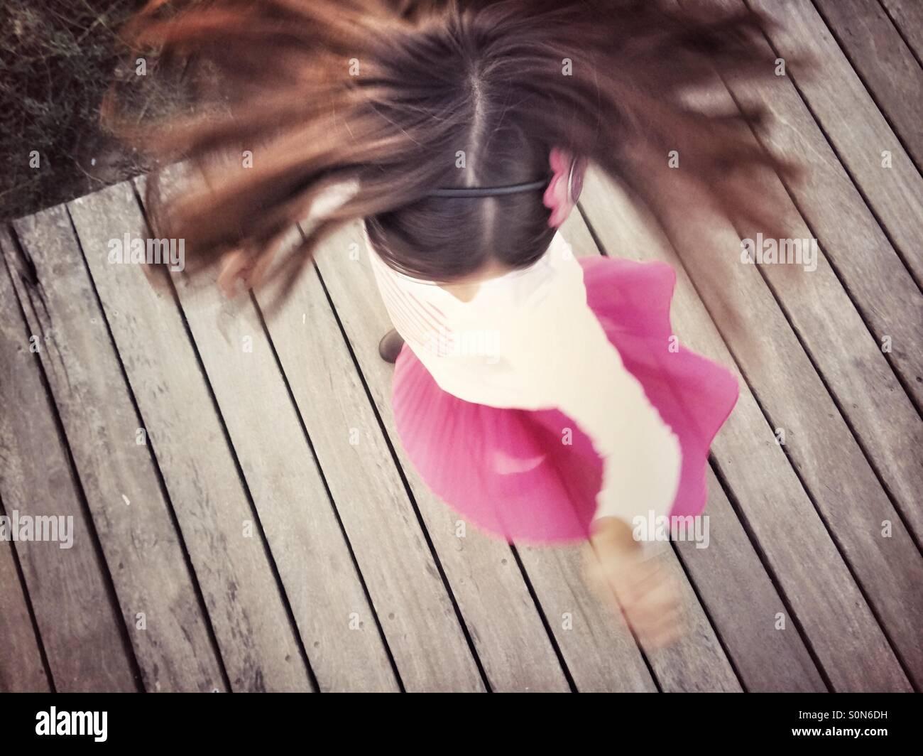 Jupe Fille en rose tournant sur le bois à pied Photo Stock