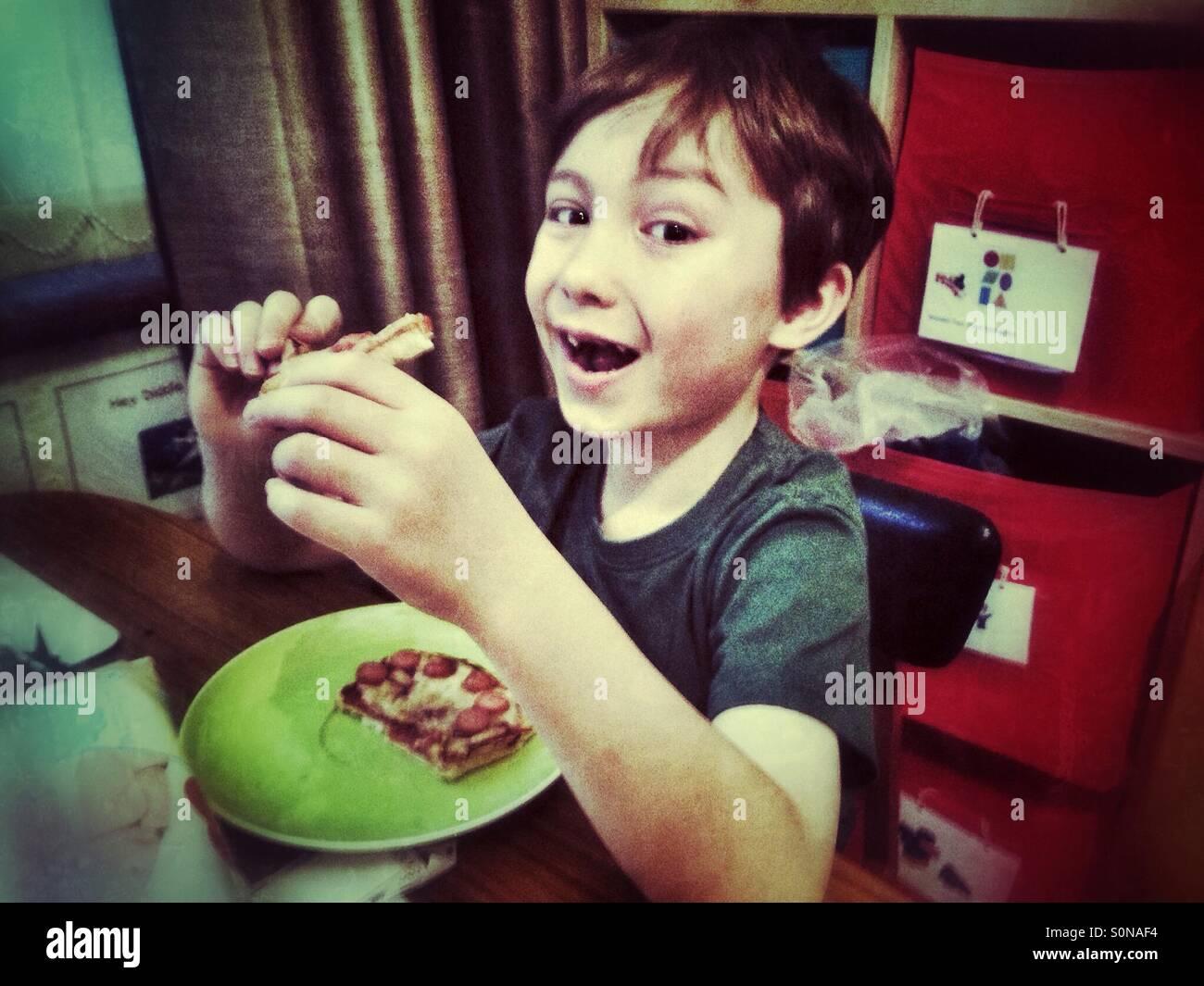 Jeune garçon de manger du pain grillé. Photo Stock