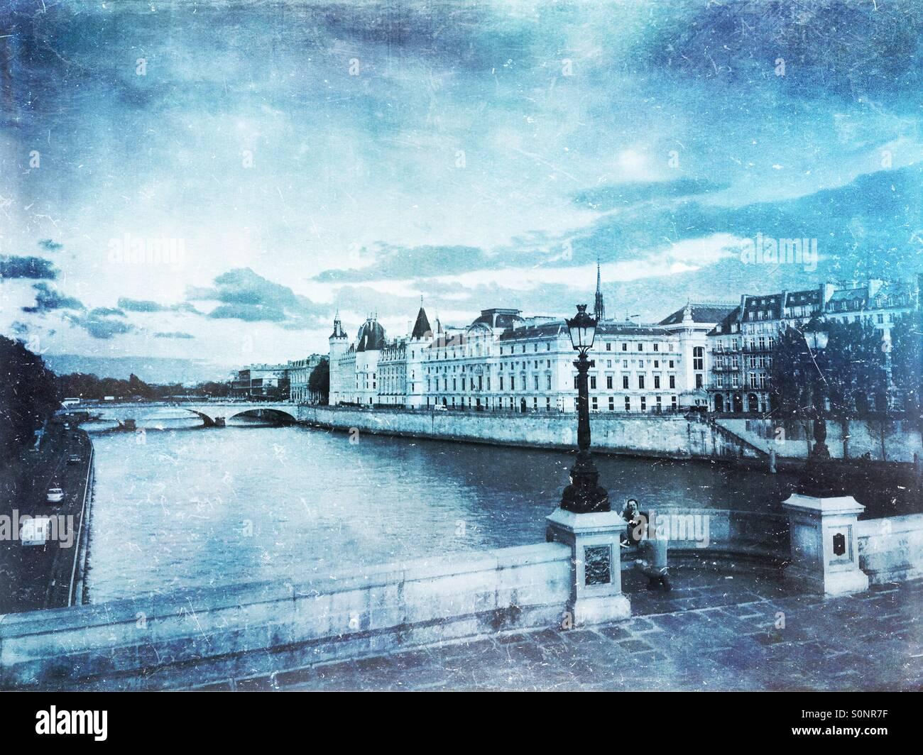 Vue de la Conciergerie sur l'Ile de la Cité à partir de l'ensemble de Seine sur le quai du Louvre. Hiver glacial d'inspiration vintage, la texture du papier calque. Banque D'Images