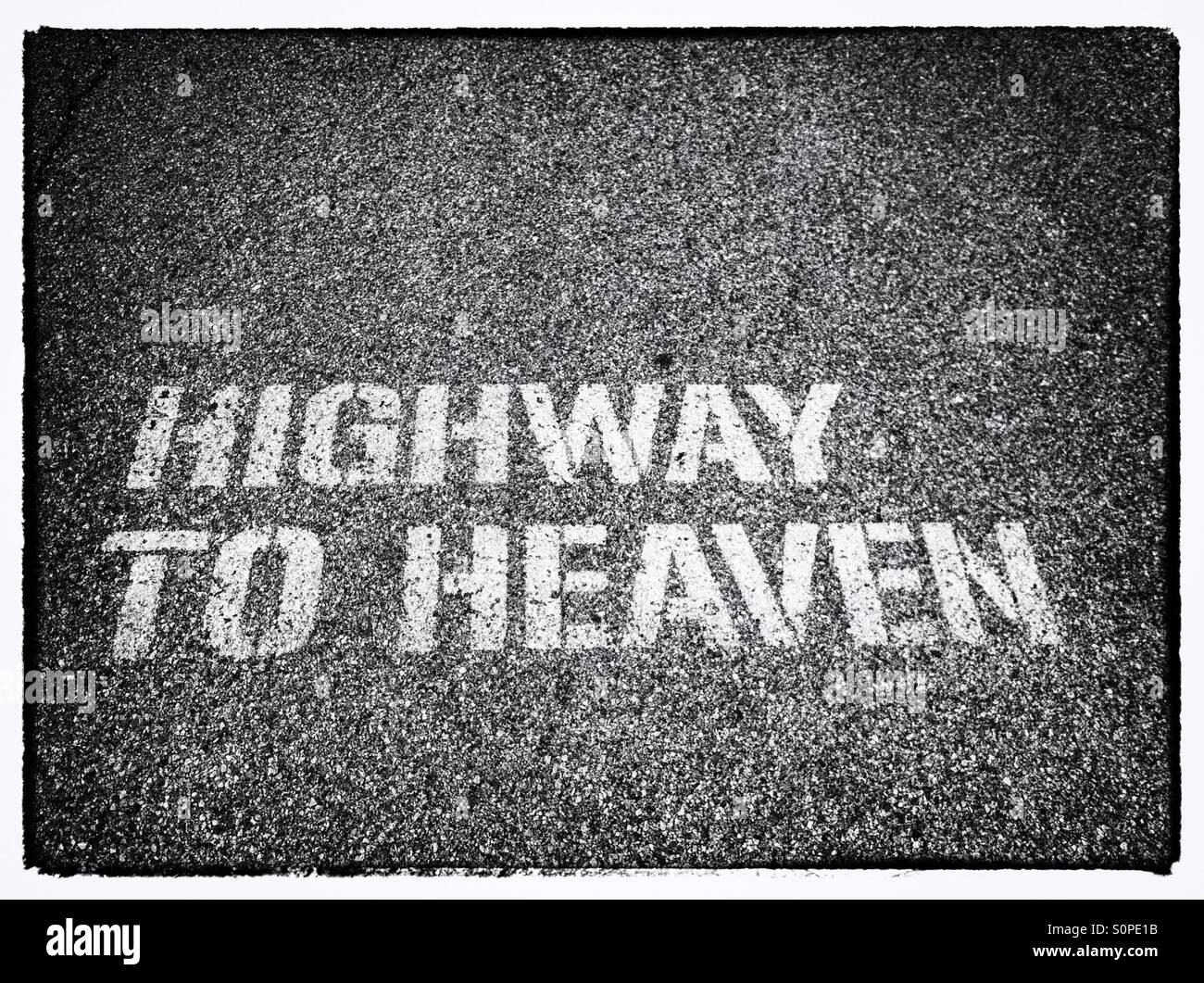 Les mots l'autoroute au Ciel en lettres blanches sur une route asphaltée Photo Stock