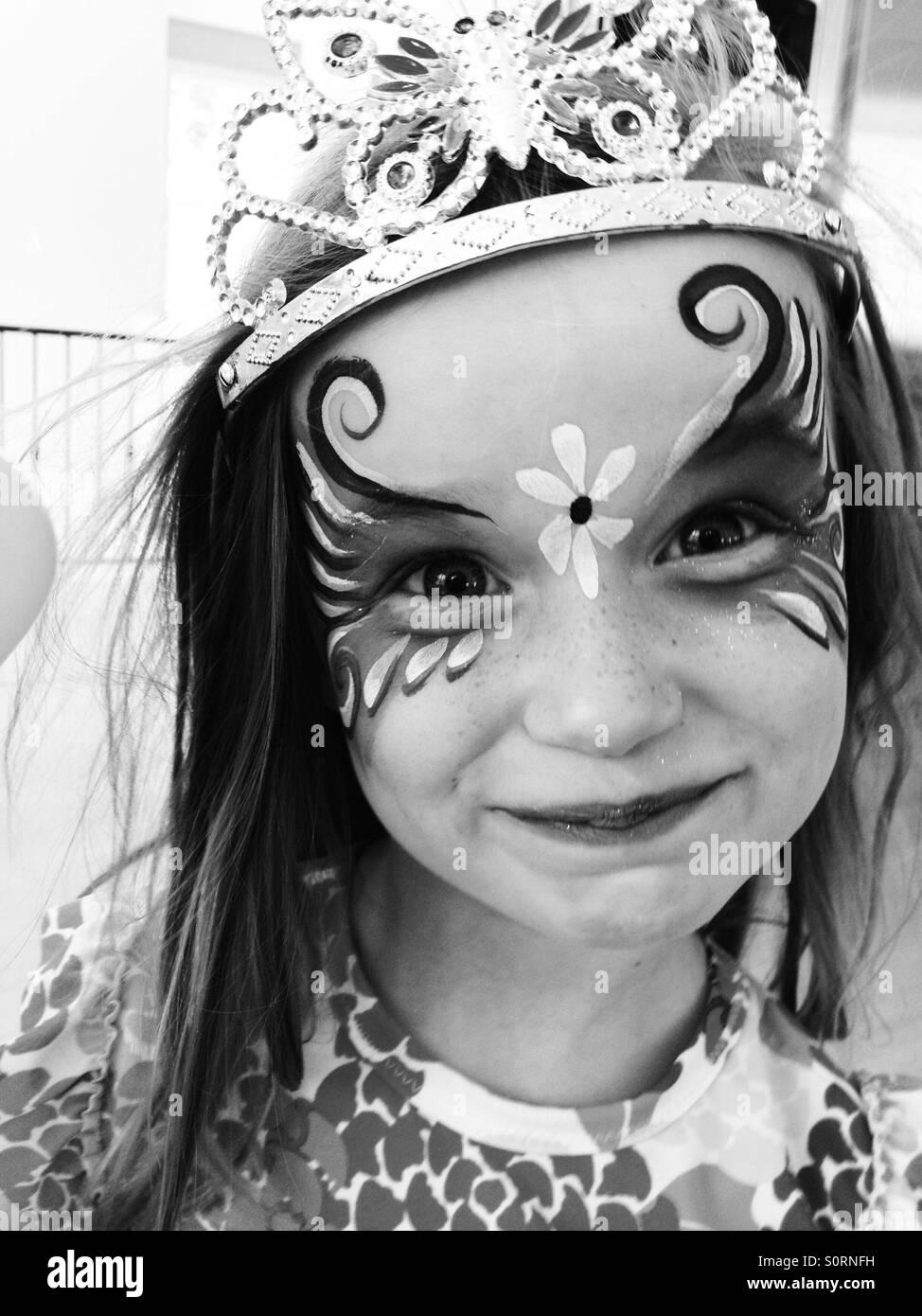 Fille avec la peinture pour le visage et tiara Photo Stock