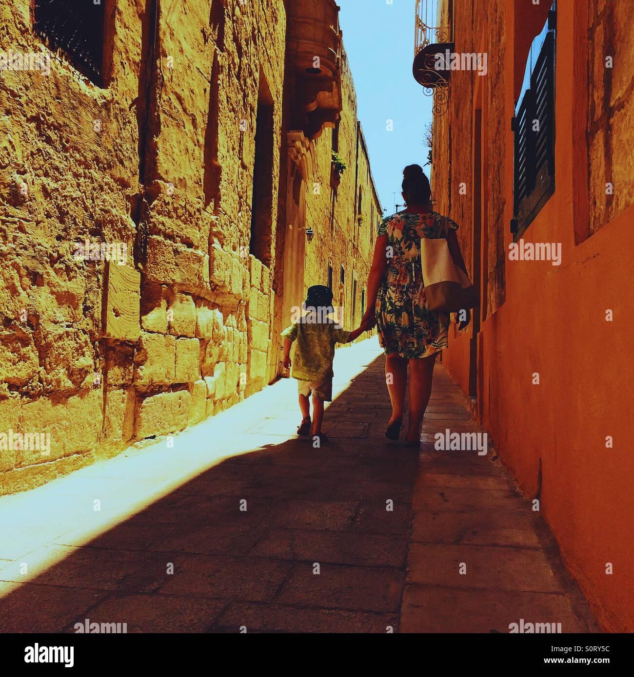 Mère et fils marche main dans la main vers le bas dans l'allée Mdina Malte Photo Stock