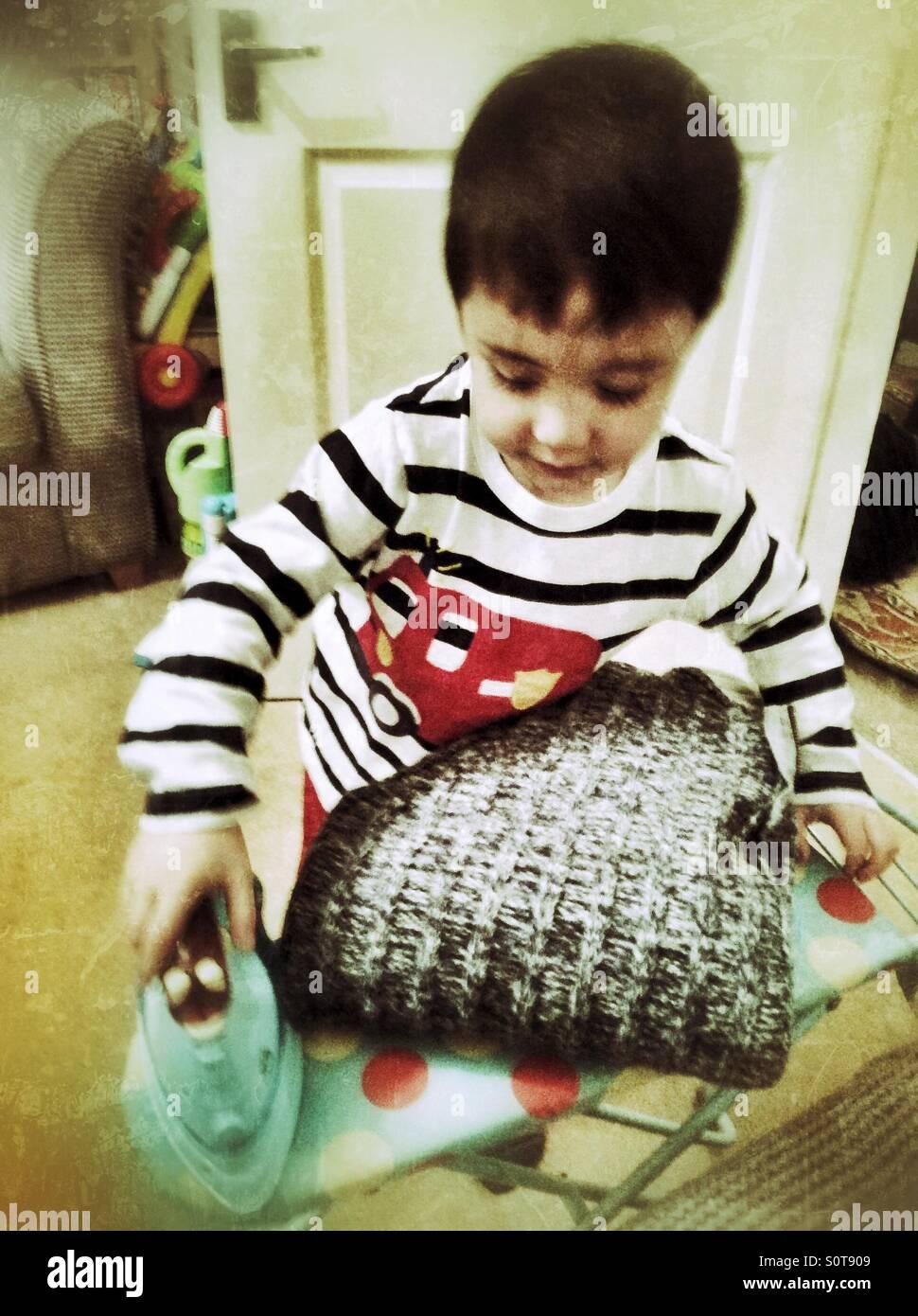 Un jeune garçon jouant avec son jouet, table et fer à repasser. Photo Stock