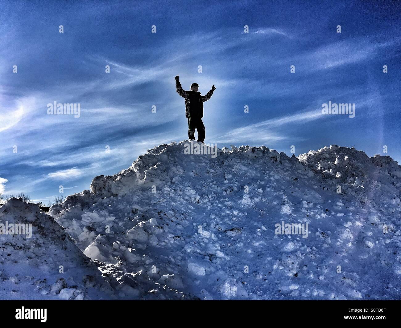 Un jeune garçon sur le dessus d'un monticule de neige massive Photo Stock