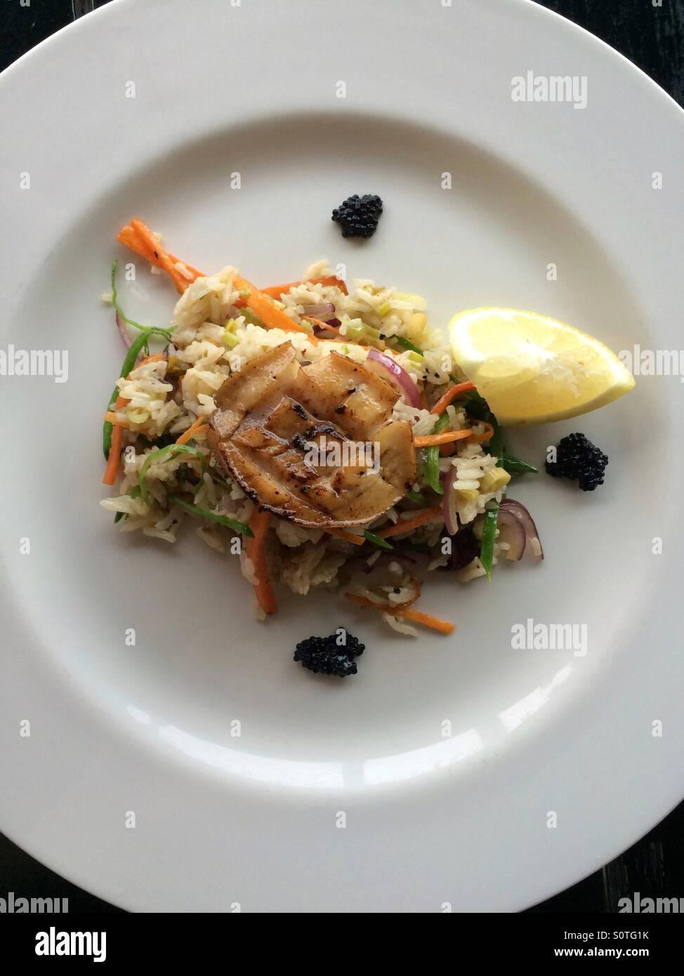 L'ormeau sur lit de riz épicé avec caviar en garniture. Photo Stock