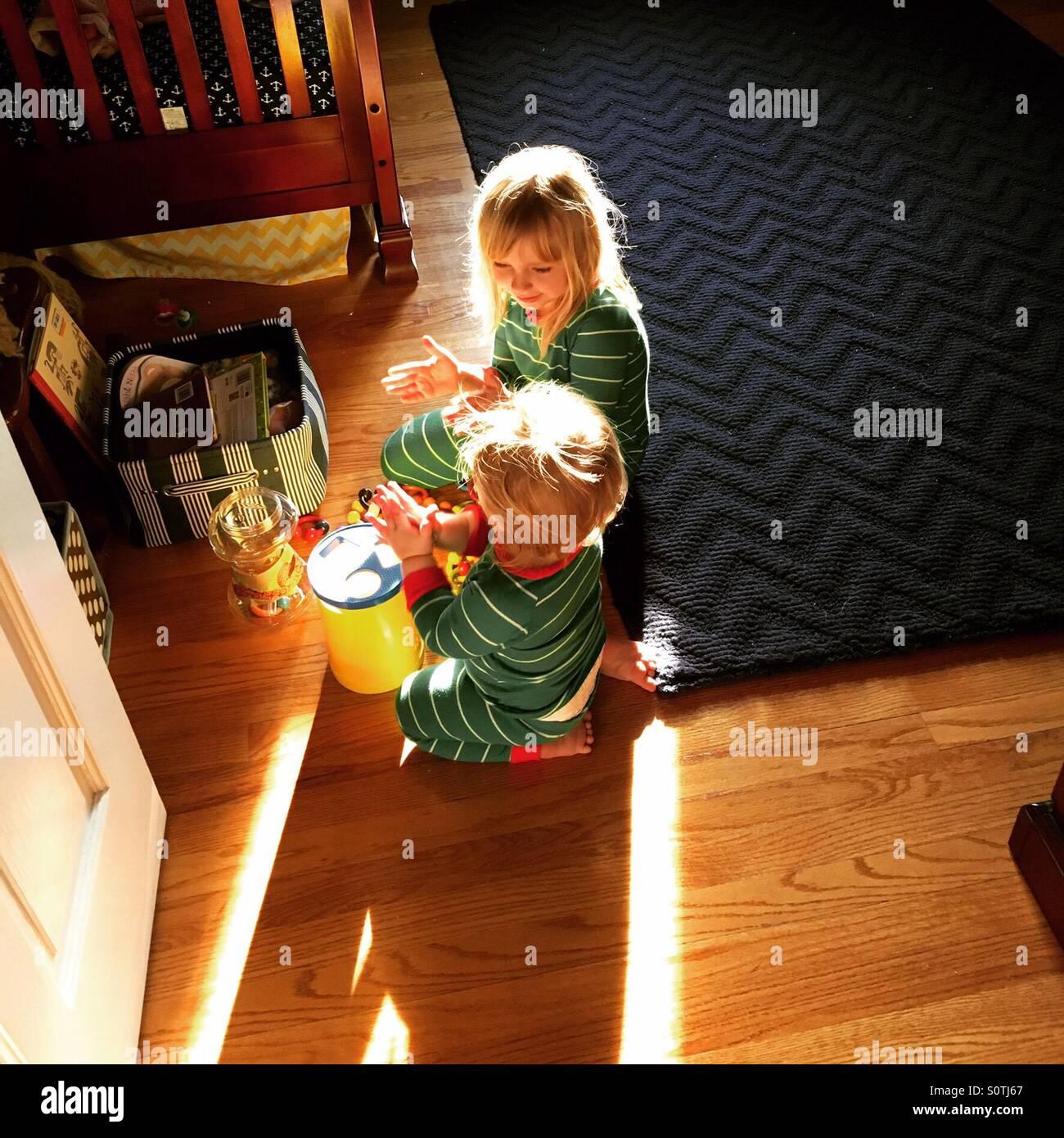 Matin jeu entre frère et soeur en pyjama correspondant Photo Stock