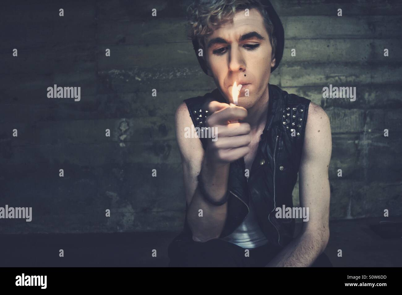 Jeune gamin en cuir gilet allumer une cigarette. Photo Stock