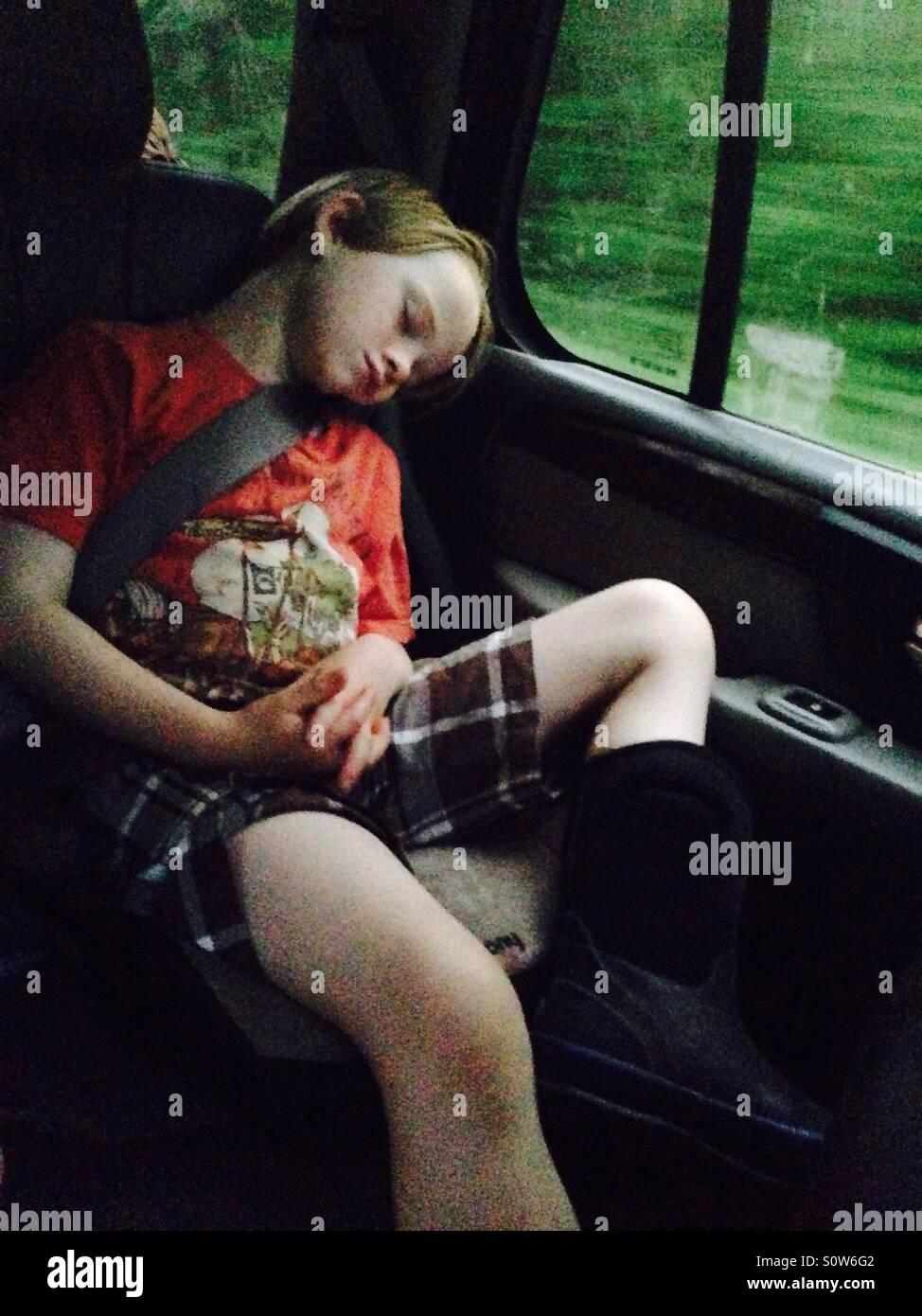 Le garçon endormi dans la voiture pendant la route Photo Stock