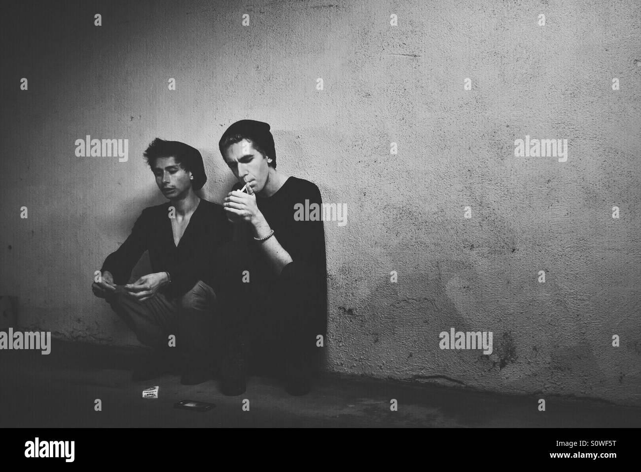 Deux jeunes hommes en noir s'asseoir contre un mur de briques. Photo Stock