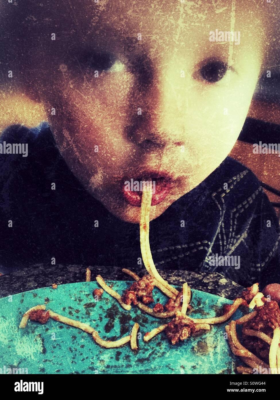 Garçon sucer un morceau de spaghetti Photo Stock