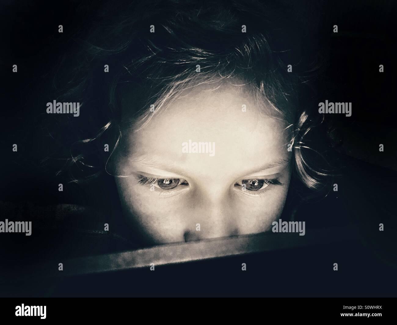 Jeune fille à la recherche intensément écran de tablette Photo Stock