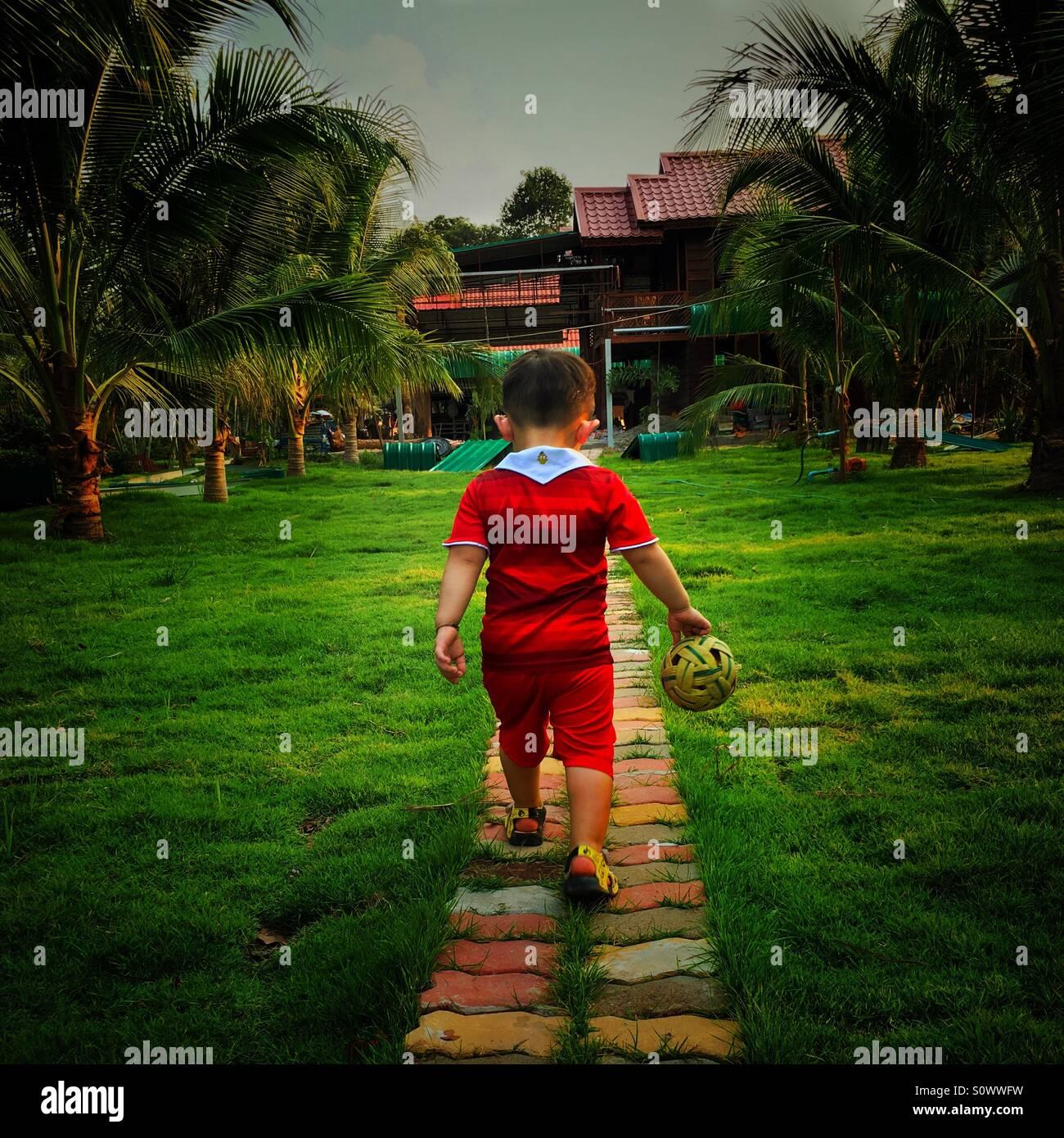 Le garçon marche avec une balle dans la main Photo Stock