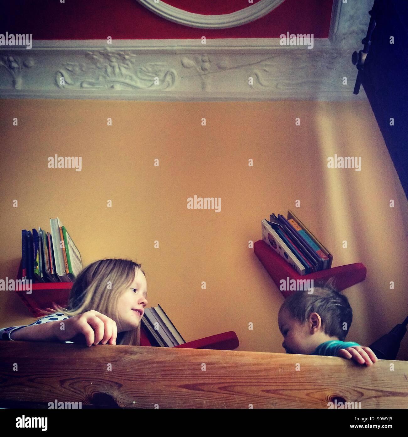 Frères et soeurs assis sur une couchette supérieure lit le matin Photo Stock