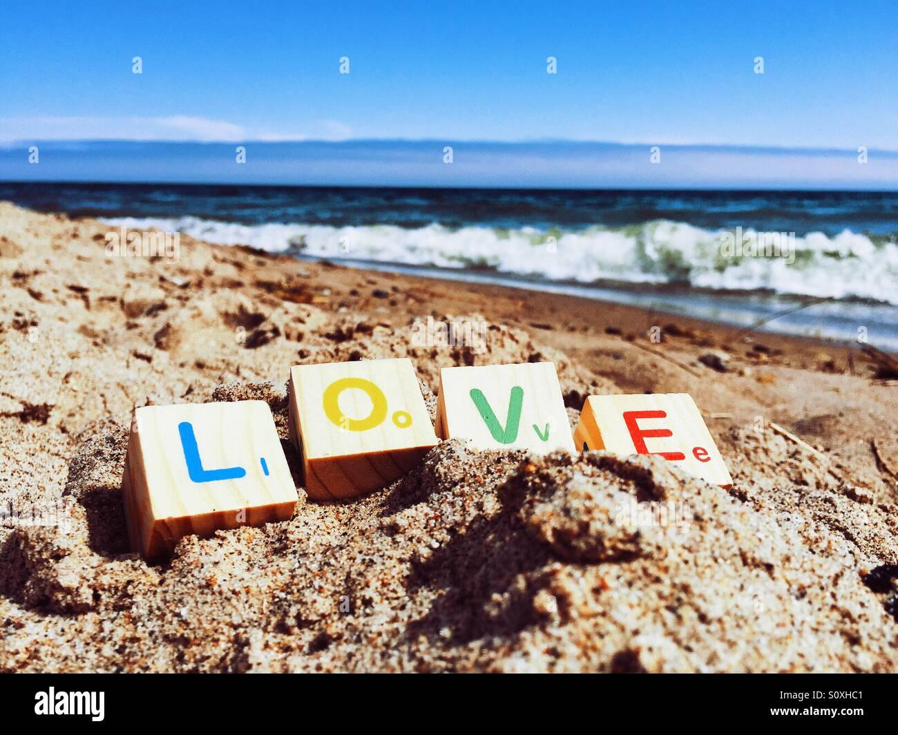 Les blocs de l'enfant l'orthographe du mot 'Amour' sur une plage de sable fin Photo Stock