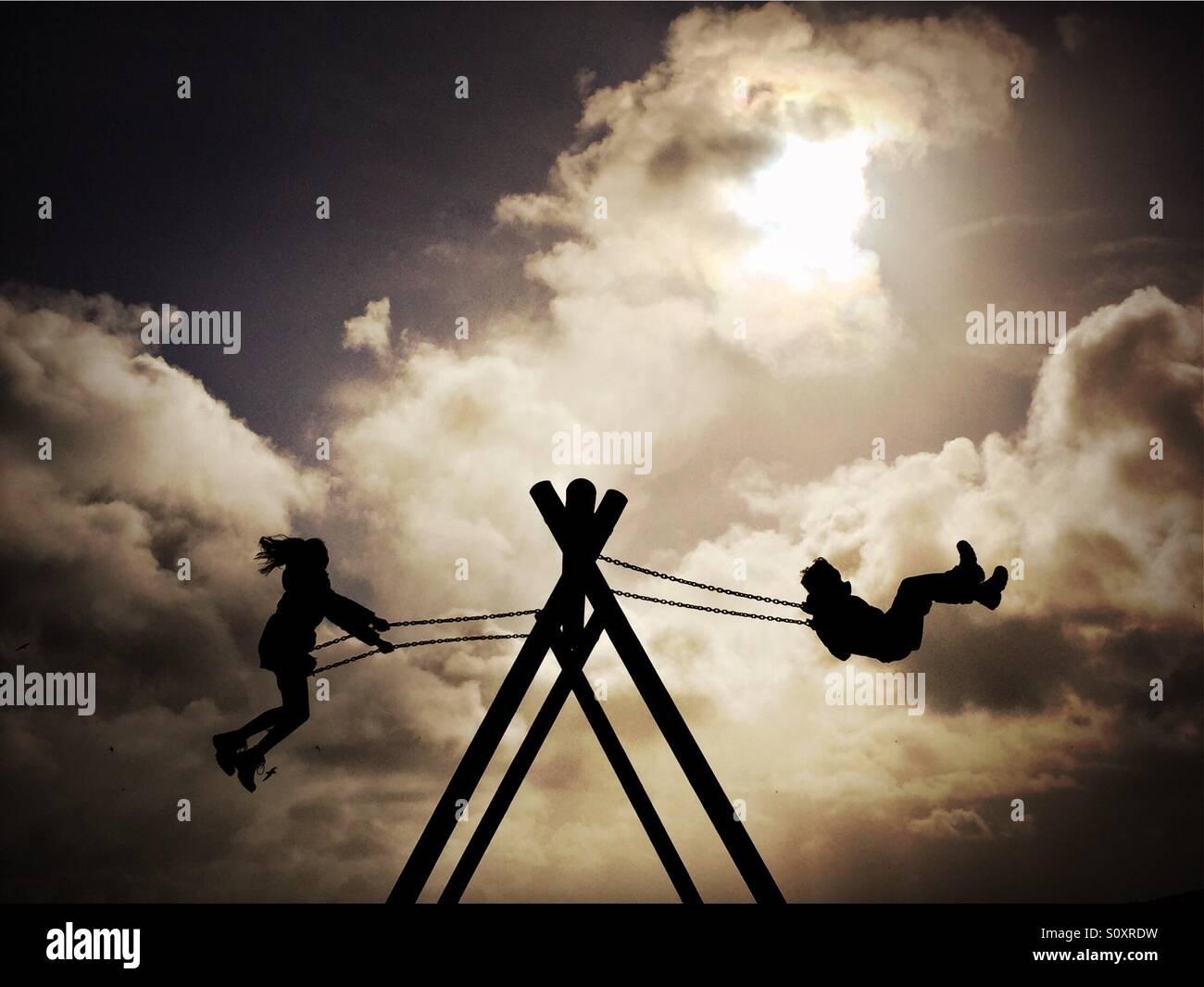 Les enfants jouent sur une balançoire dans un parc de vacances à Loch Ken, en Écosse. Photo Stock