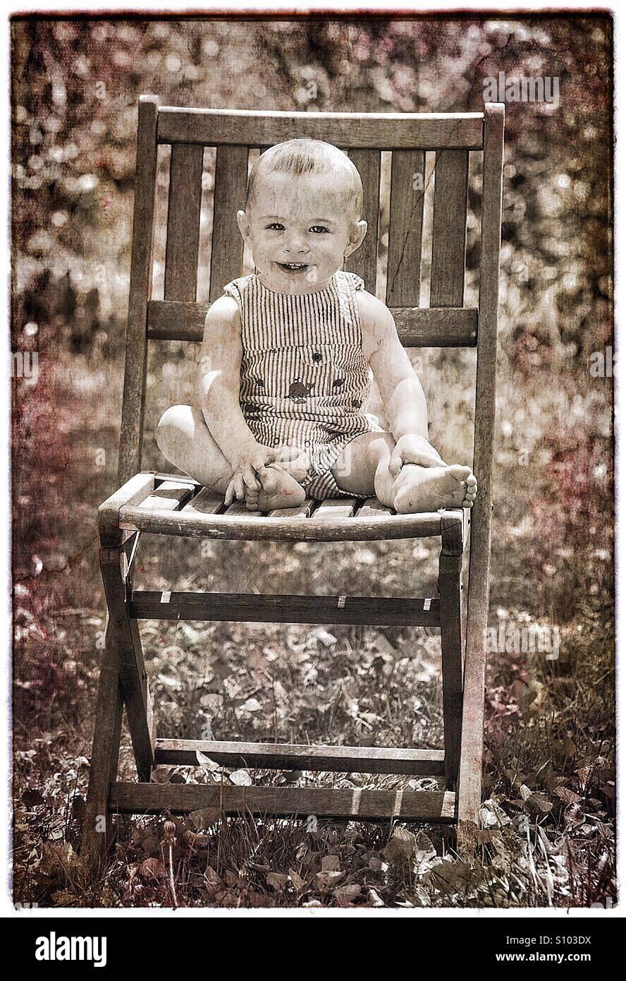 Bébé avec grand sourire assis sur une chaise à l'extérieur. Photo Stock