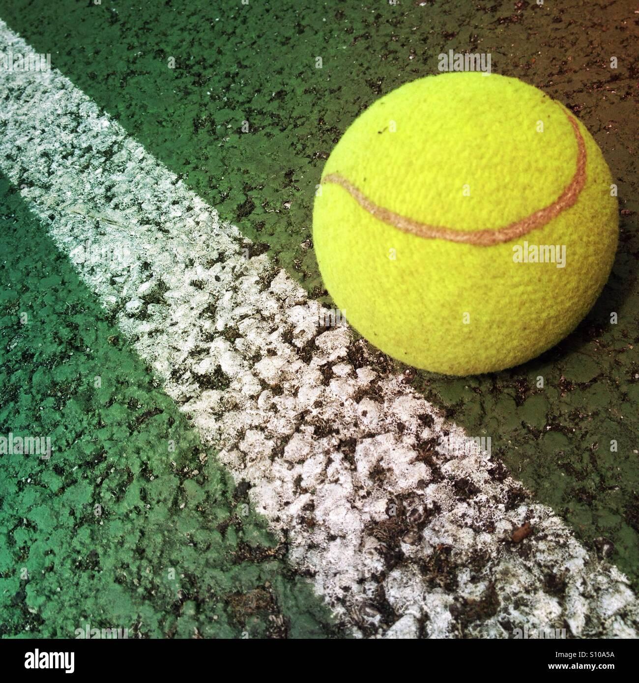 Balle de tennis sur le côté d'une ligne de tennis Banque D'Images