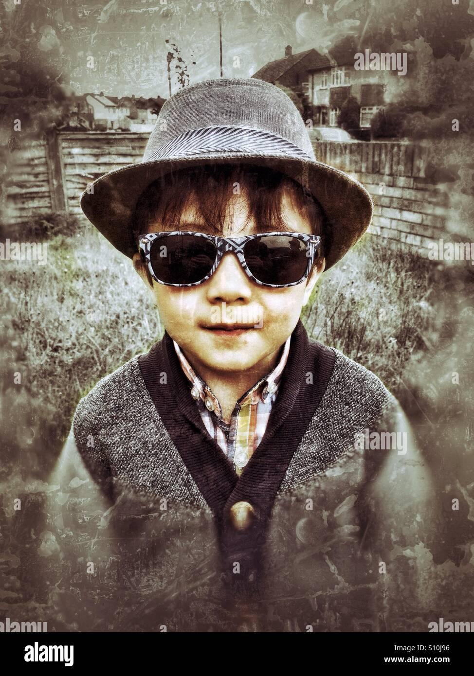 Un jeune garçon portant un chapeau et des lunettes de soleil. Photo Stock
