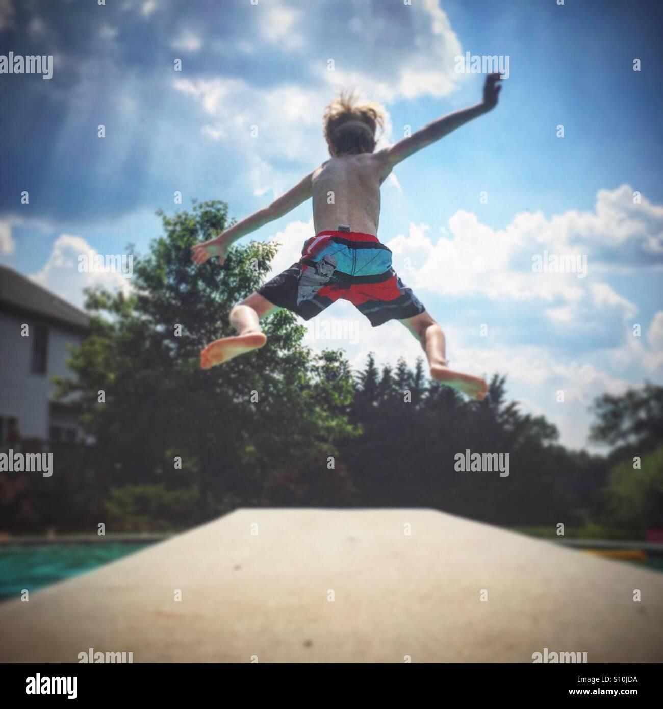 Un jeune garçon saute d'un plongeoir et dans une piscine par une chaude journée d'été Photo Stock