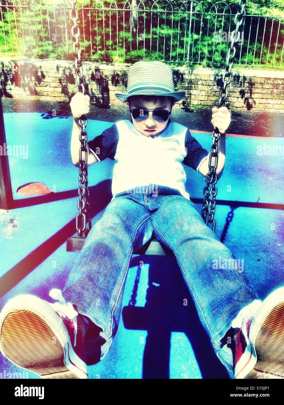 Un jeune garçon portant des lunettes de soleil et chapeau joue sur balançoire dans le parc. Photo Stock