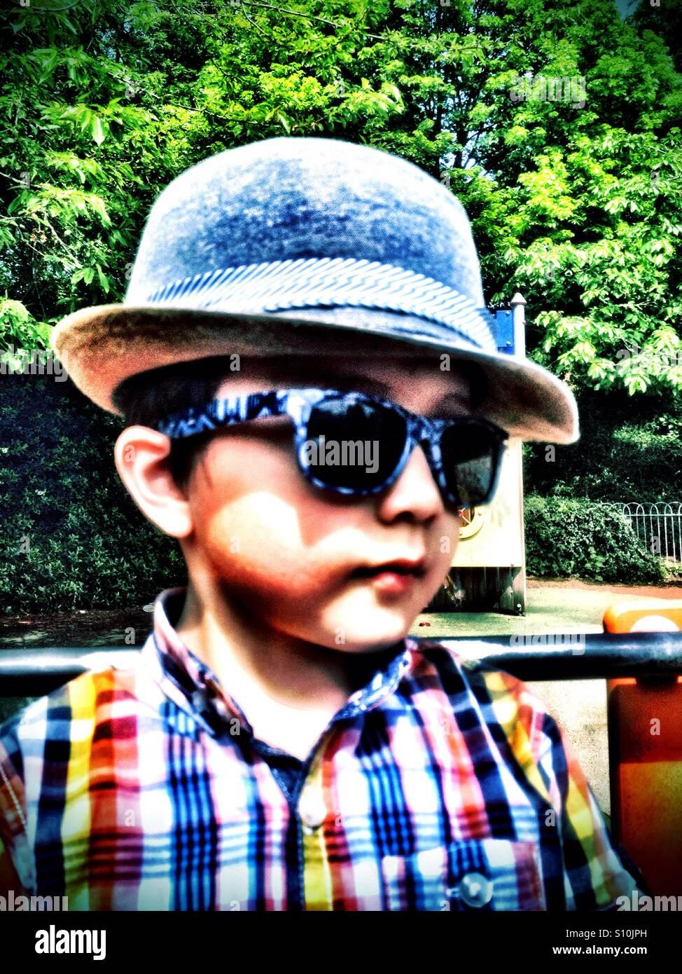 Un jeune garçon dans le parc portant chapeau et des lunettes de soleil. Banque D'Images