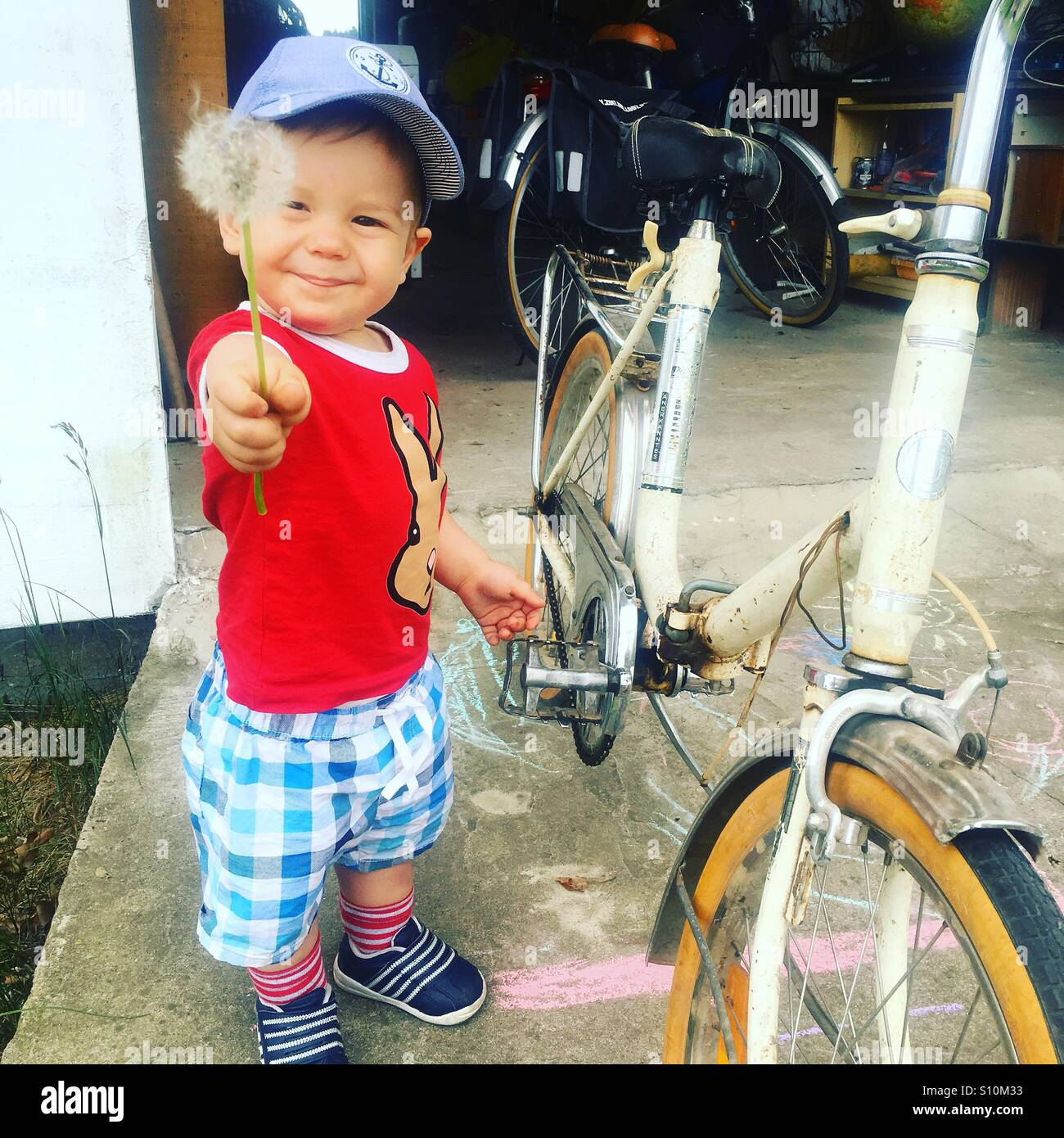 Tout-petit avec une fleur dans sa main , debout à côté d'un vieux vélo, en face du garage Photo Stock